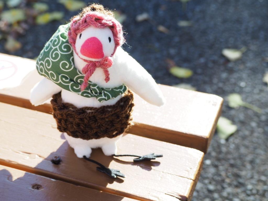 暖かそうな腹巻きと帽子を着用したふろしき文鳥が上野動物公園のベンチに座る
