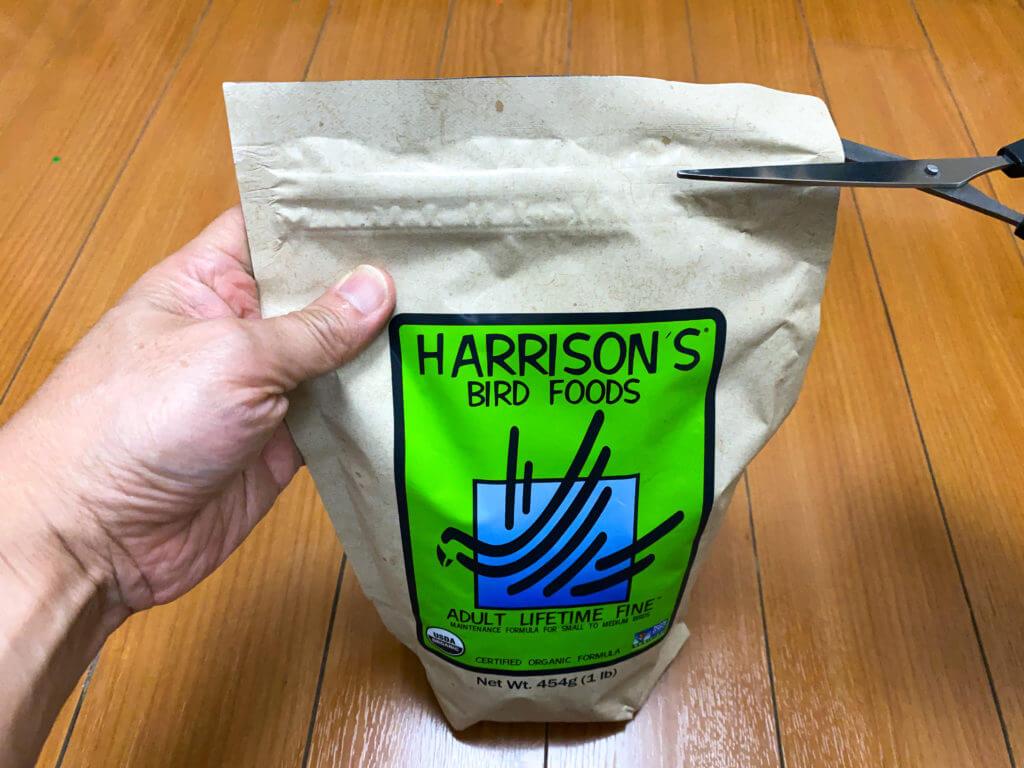ペレット(ハリソン)の封をハサミで切ろうとしている